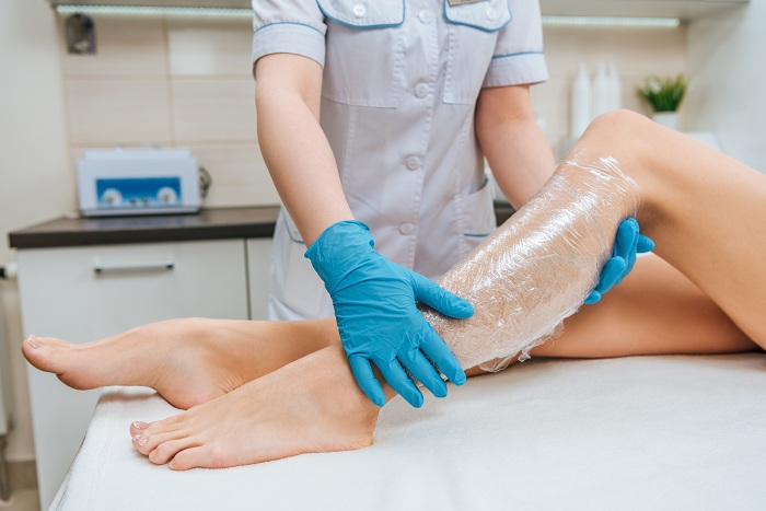 Cosmetologists using body plastic wraps to treat patients