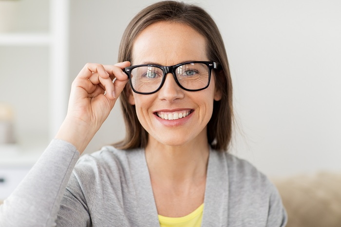 Happy middle aged woman in glasses at home