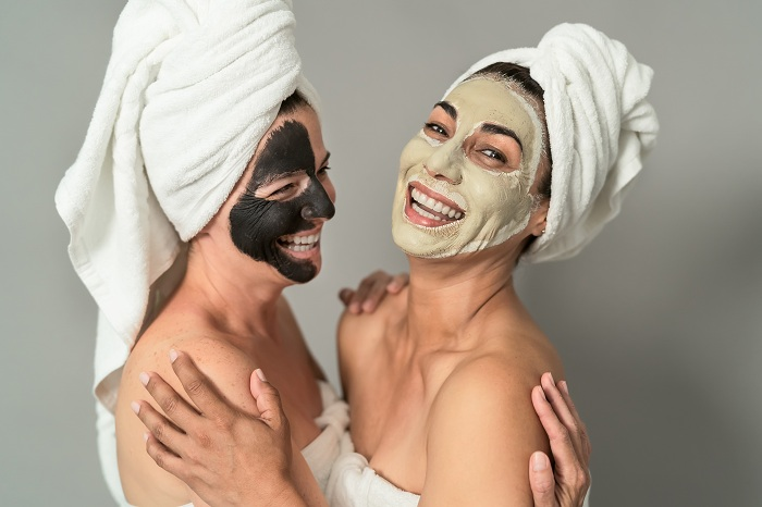 Happy middle aged women on facial mask at the spa