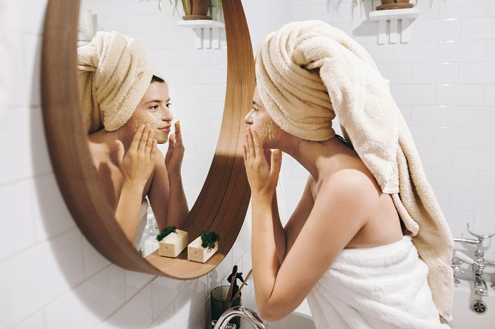 Happy woman applying face mask overnight