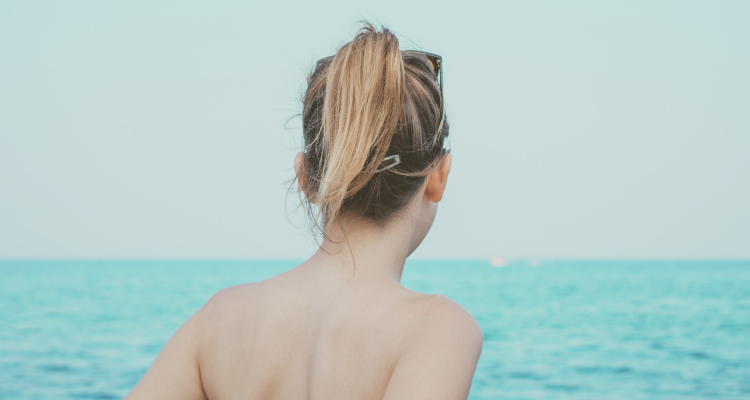 smooth back of woman facing ocean