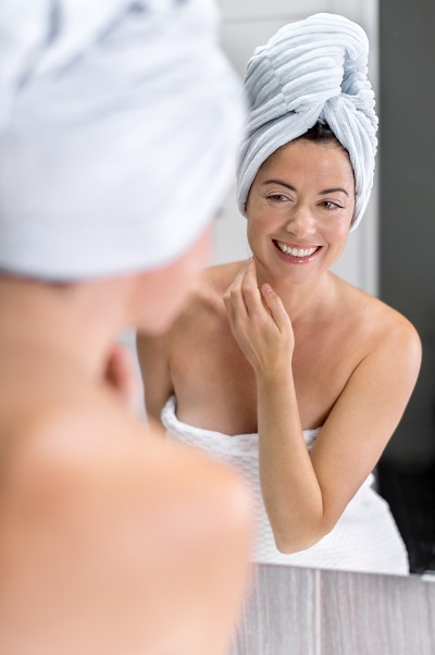 Pretty mature woman looking at herself in the bathroom mirror