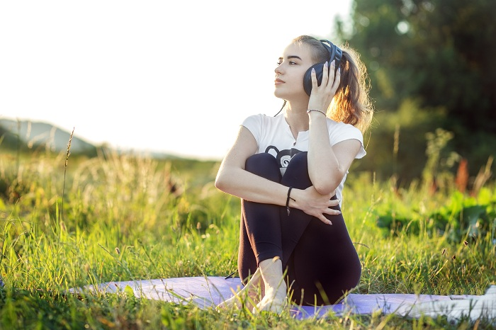 Woman doing yoga and music theraphy outdoors