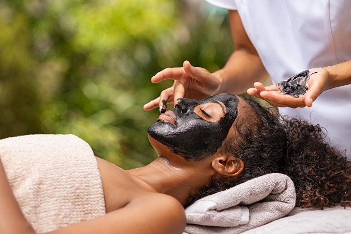 Woman getting charcoal facial treatment