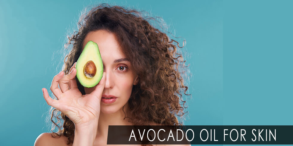 Woman holding a slice of avocado fruit