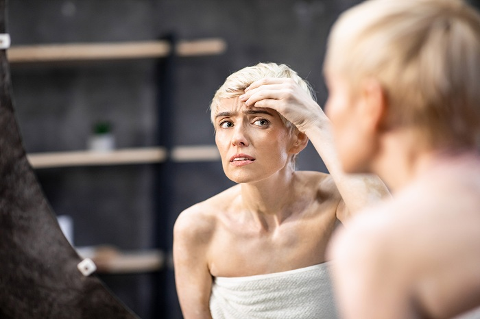 Woman Looking At Wrinkles Touching Face Standing In Bathroom Indoor