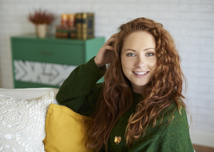 Woman with freckles sitting on a couch
