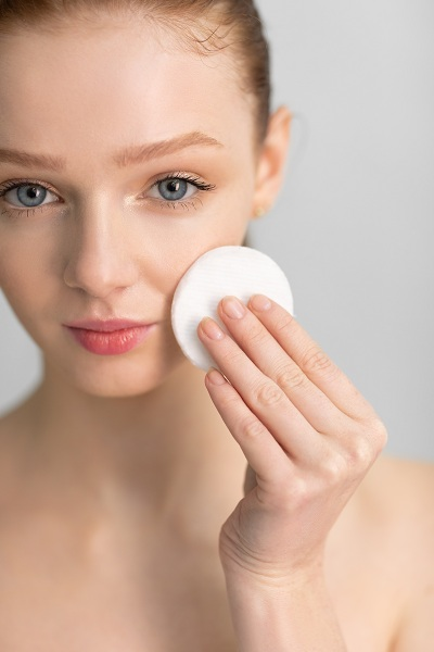Young woman cleansing skin face with a cotton pad