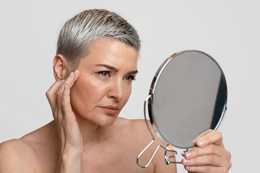 aging woman looking at her mirror to check her skin