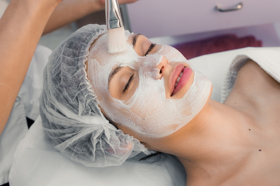 applying mask on a woman's face at the spa