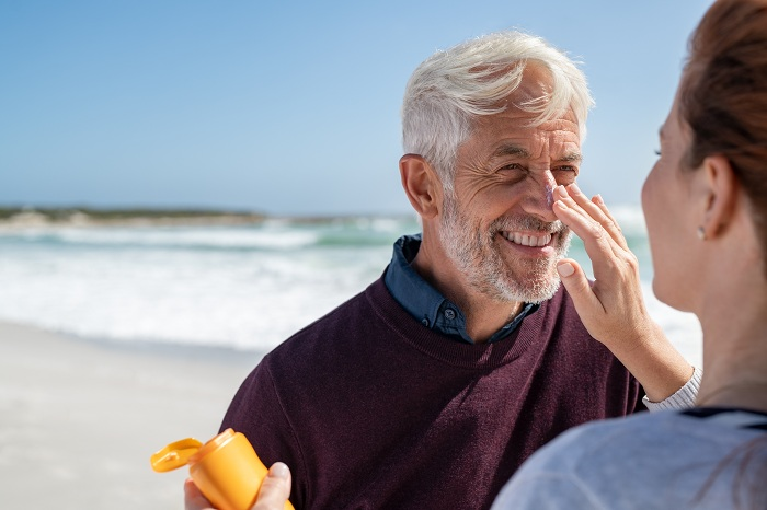 applying sunscreen cream on a middle aged man's face