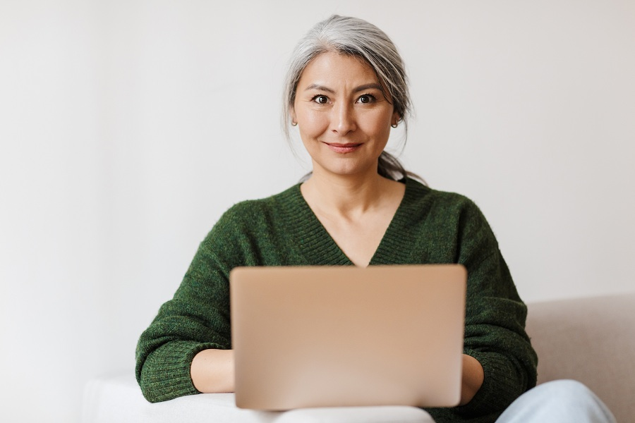 Asian woman using her laptop on a sofa
