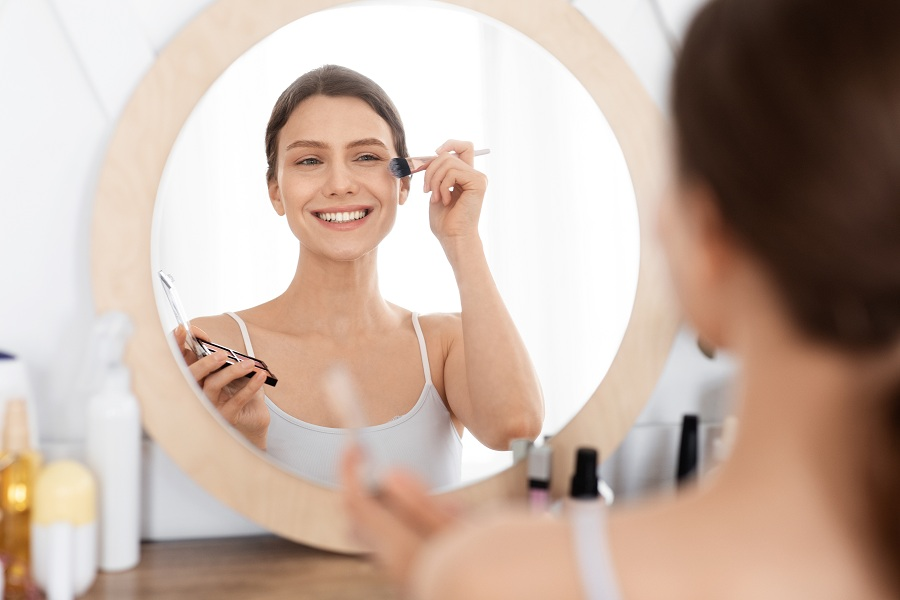 attractive lady doing light makeup before going out