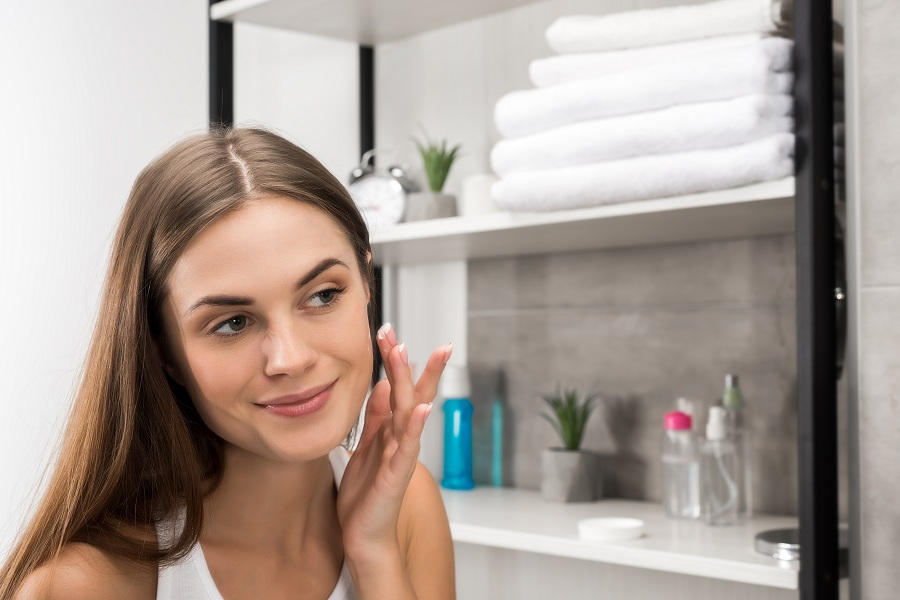 beautiful woman with clear skin applying cream on face