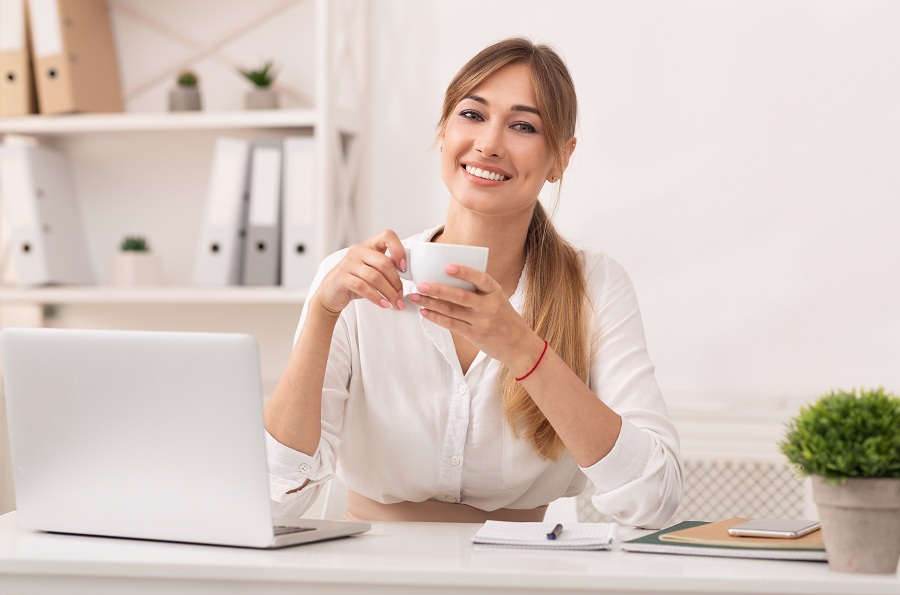 business woman holding coffee and smiling at her office