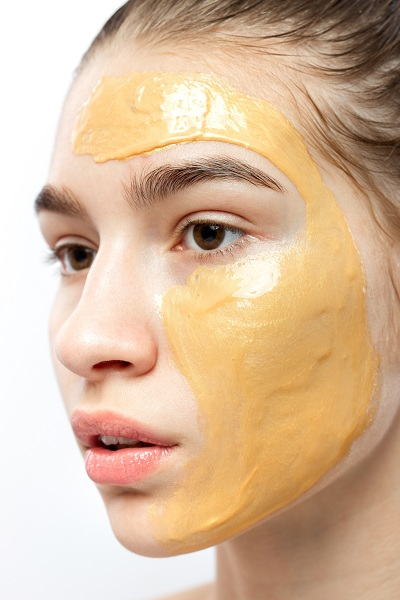 The face of a young girl with yellow cosmetic mask on it