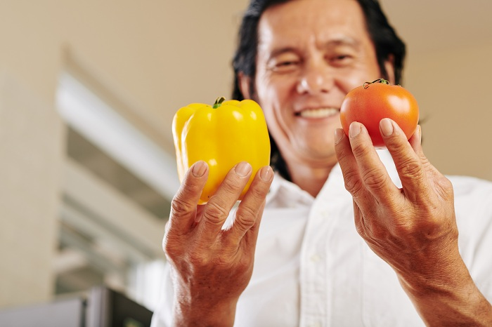 man holding veggies rich in vitamins a and e