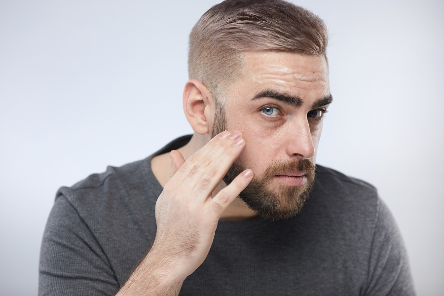 man using skincare products