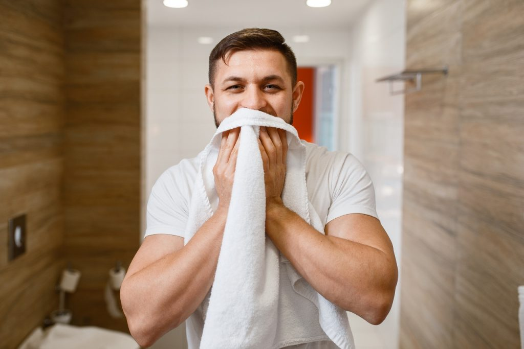Man wipes his face with a towel