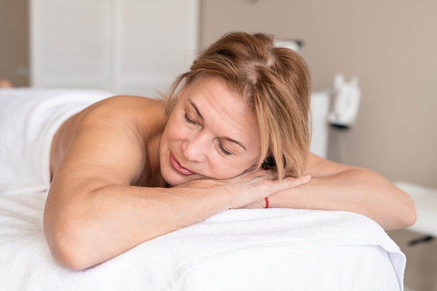 Calm mature woman skin on massage table