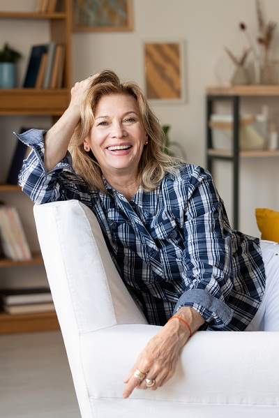 middle aged woman on a couch smiling
