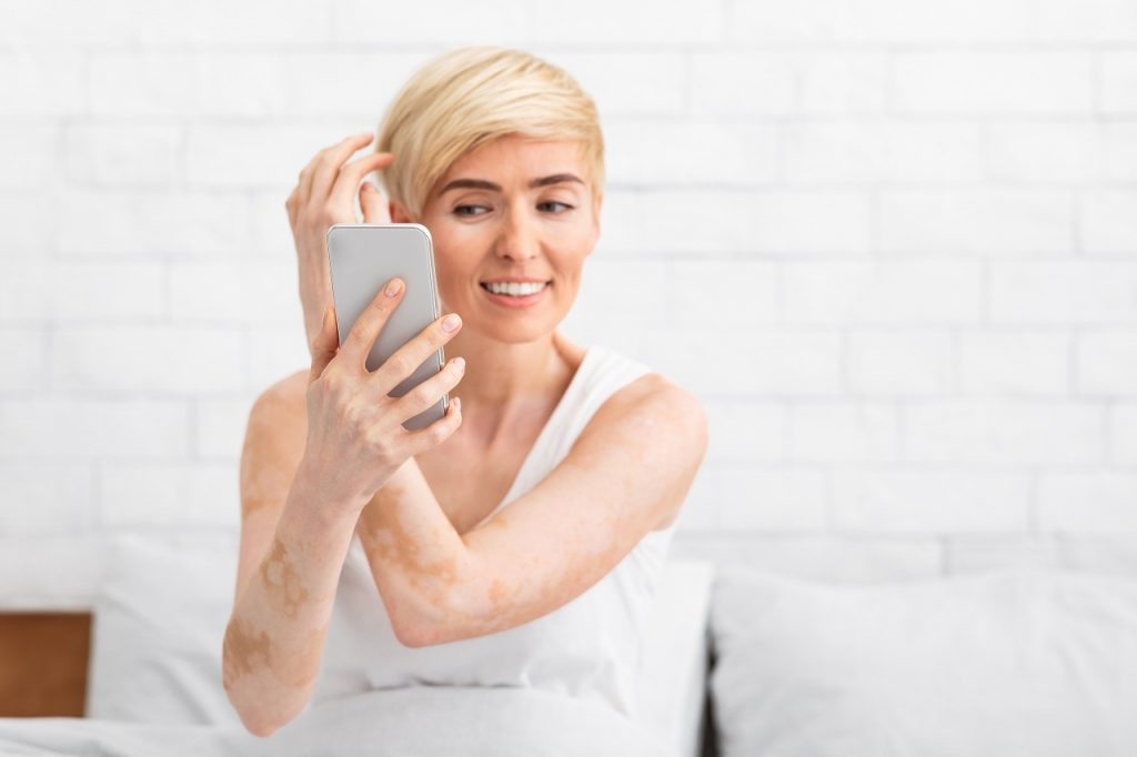 Middle-aged woman touching hair smiling looking in cellphone