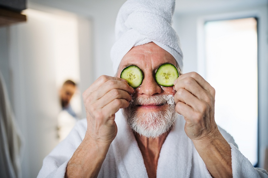 old man with cucumber home remedy for eyebags