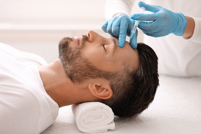 Plastic surgeon injecting hyaluronic acid in man forehead