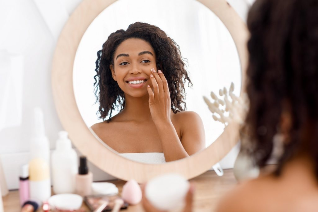 pretty black woman applying moisturizer on her face in the morning