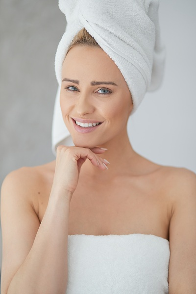 Beautiful middle aged blonde woman wrapped in towel white towel
