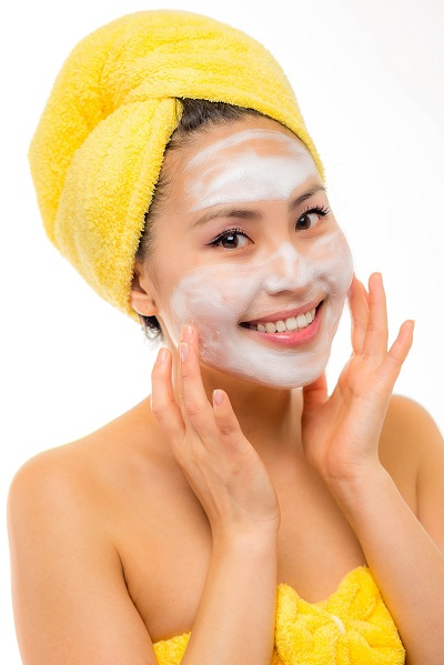 pretty woman applying facial wash for her skincare routine