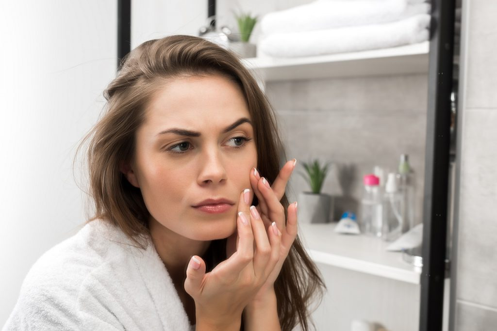 Woman checking face skin and looking at the mirror