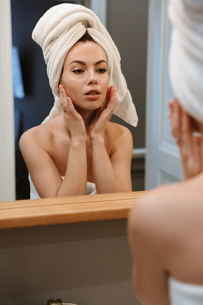 pretty woman in white towels in front of a mirror in the bathroom