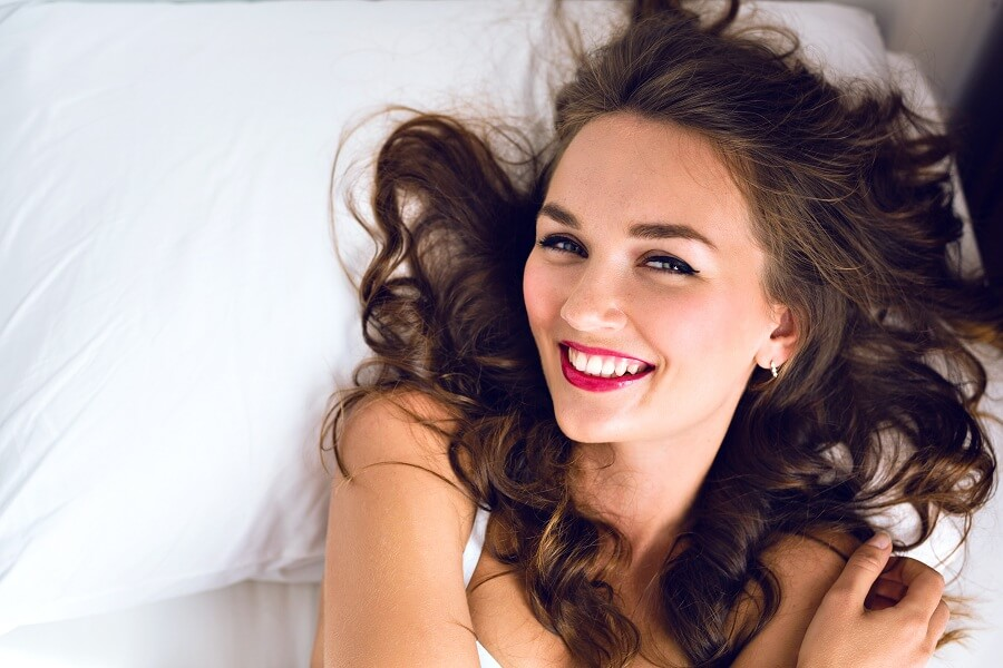 pretty woman on bed after waking up in the morning