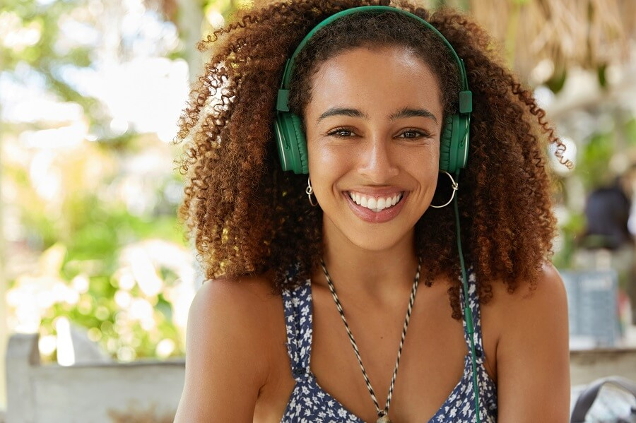 pretty young african american woman with green headphones