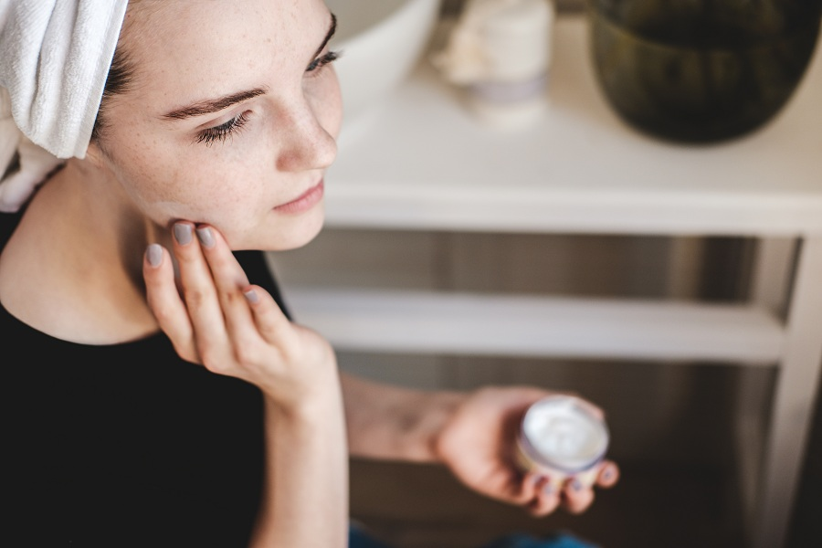 pretty young woman applying cream on her face