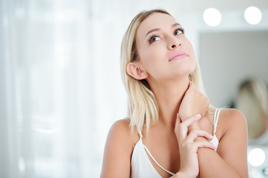 pretty young woman at home touching her neck