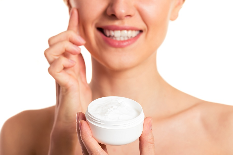 pretty young woman with face cream