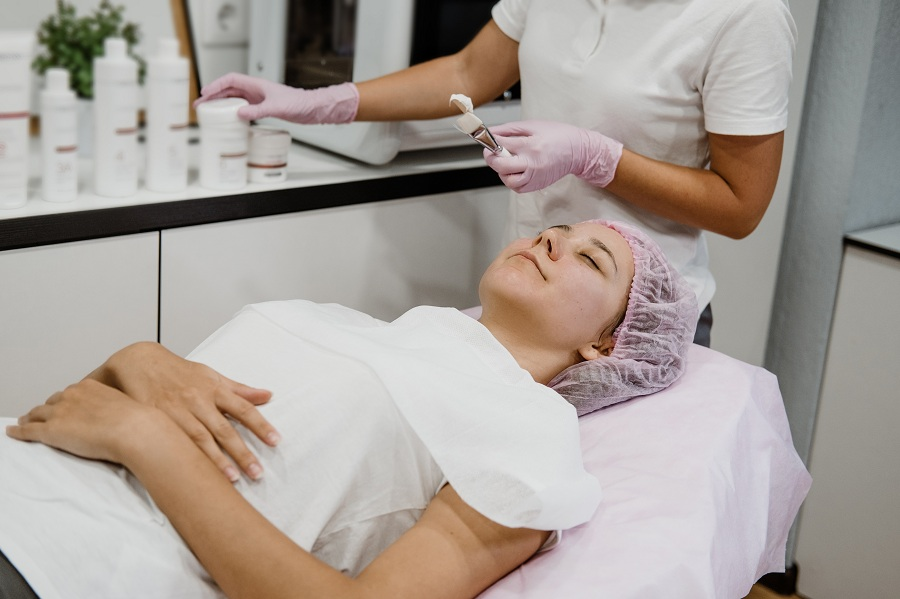 Professional Esthetician Apply Face Mask to the client's face in spa beauty center. Young woman getting facial care by beautician at spa salon Acne Treatment