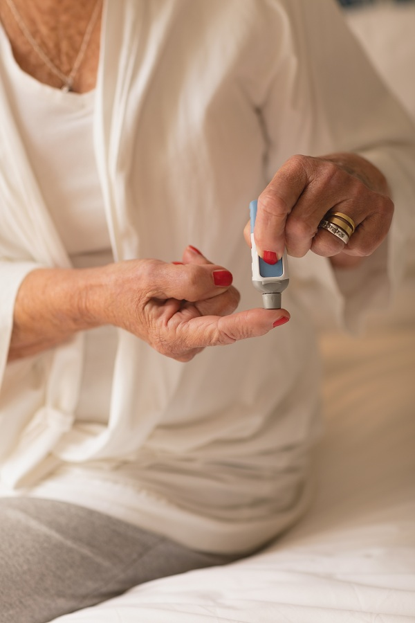 Mid section of senior woman applying cream on her finger at home