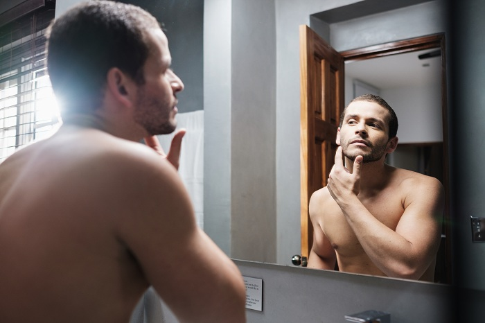 Shirtless Man Looks at Himself in Front of Mirror