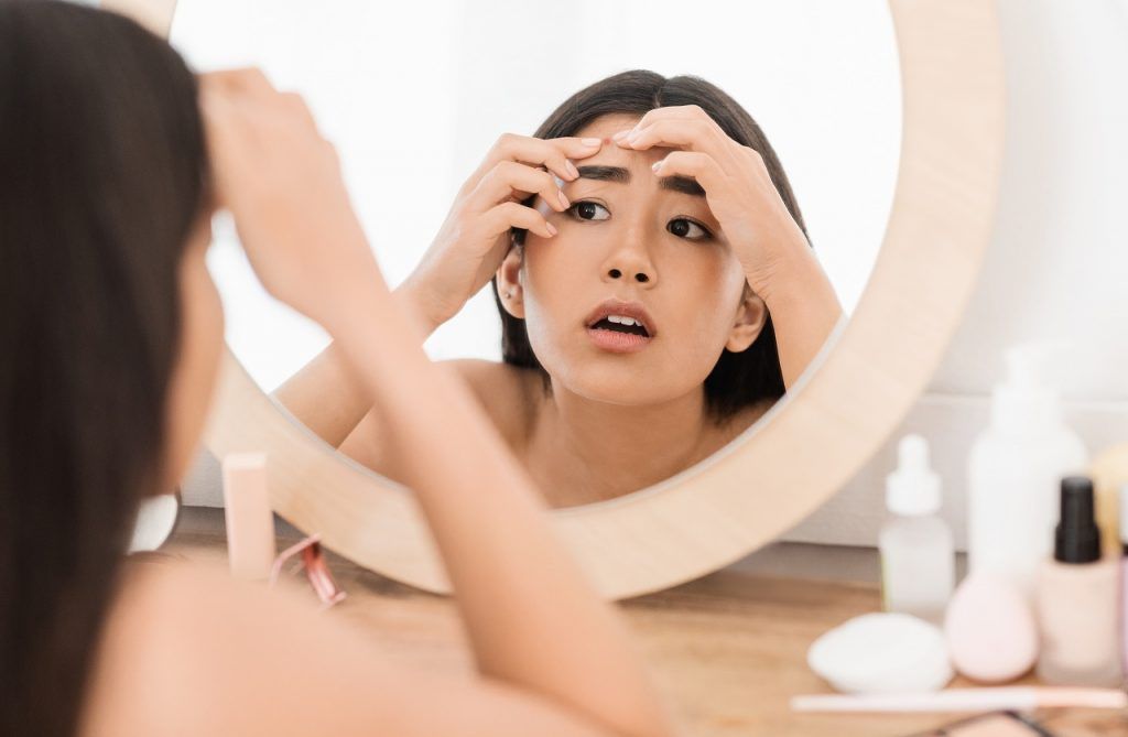 young woman checking her pimples in the mirror