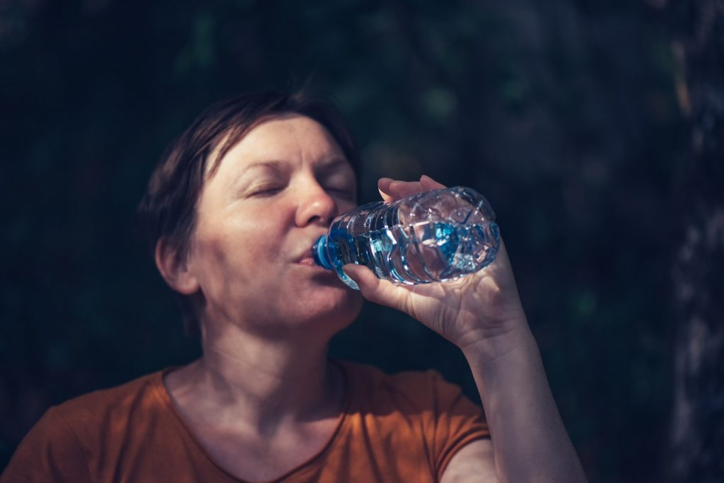 woman drinking water outdoors to combat heat