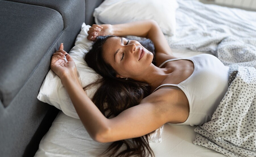 woman sleeping on her back smiling