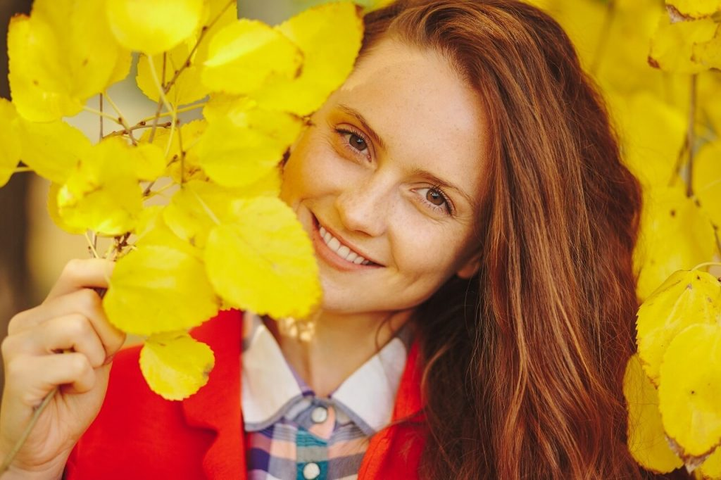 woman smiling on a photoshoot with yellow flowers