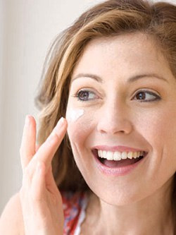 Woman applying beauty cream on her face