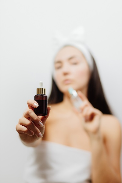 woman using face serum as skin care routine