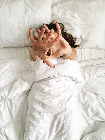 Woman waking up in a white and clean bed