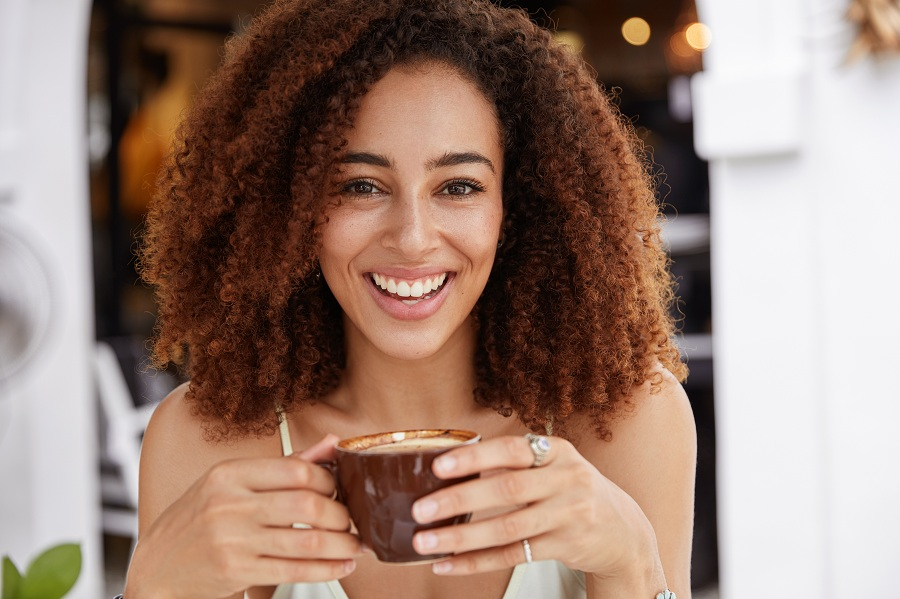 young African American female model has dark healthy skin, white teeth, drinks aromatic espresso, spends leisure time in coffee shop