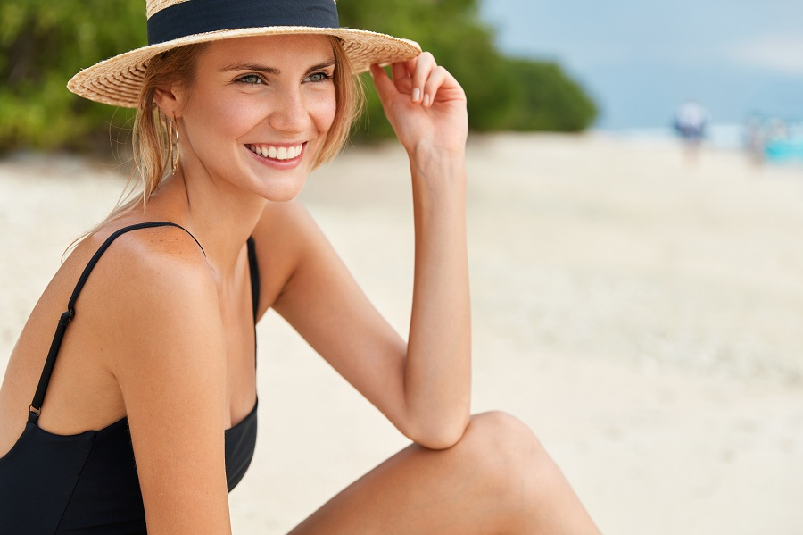 Cute young woman wears bathing suit, has positive smile on face and fresh tanned skin, admires good rest at ocean beach